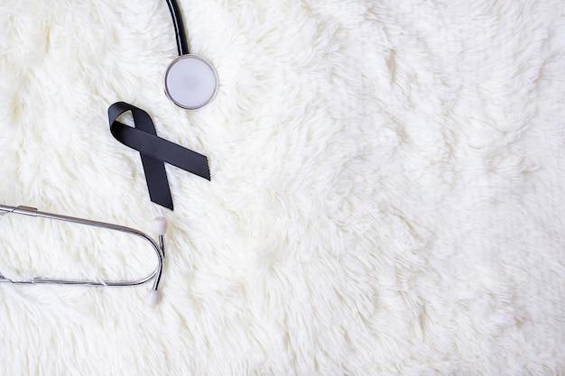 Ruban noir et stéthoscope sur fond de fourrure blanc