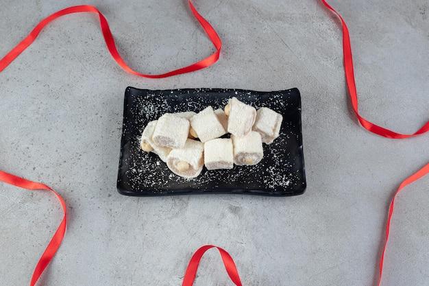 Ruban posé autour d'un plateau noir de guimauves sur une surface en marbre