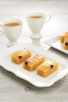 Ruban prol fait maison tranché focus sélectionné ou bolu tapai sur plaque blanche. prol tape est un gâteau traditionnel d'indonésie, fabriqué à partir de manioc fermenté