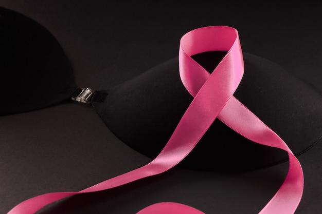 Ruban rose sur un soutien-gorge noir pour soutenir une campagne de sensibilisation au cancer du sein et du sein en octobre.
