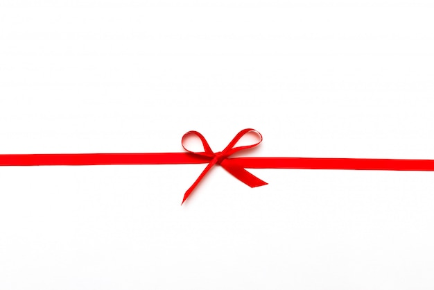 Ruban rouge ou corde attachée à l'arc isolé sur blanc