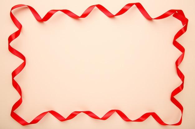 Ruban rouge sur fond beige avec espace copie