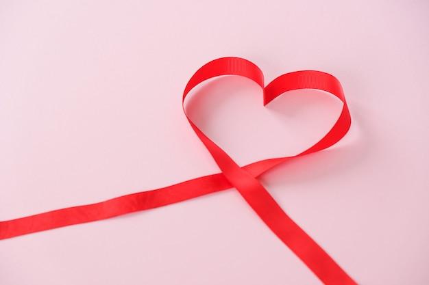 Ruban rouge en forme de coeur sur fond rose
