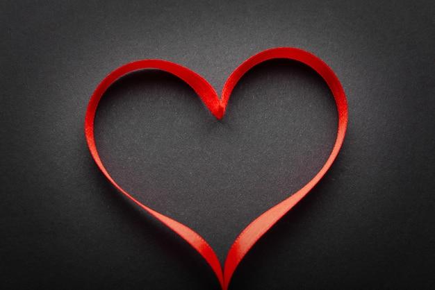 Ruban rouge en forme de coeur sur une surface grise