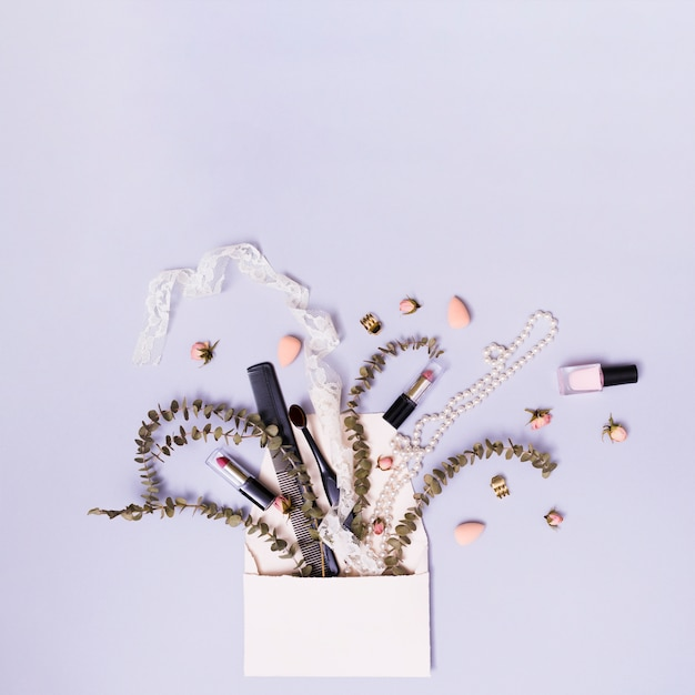 Ruban; rouge à lèvres; peigne; collier avec brindille et fleurs sortant de l'enveloppe