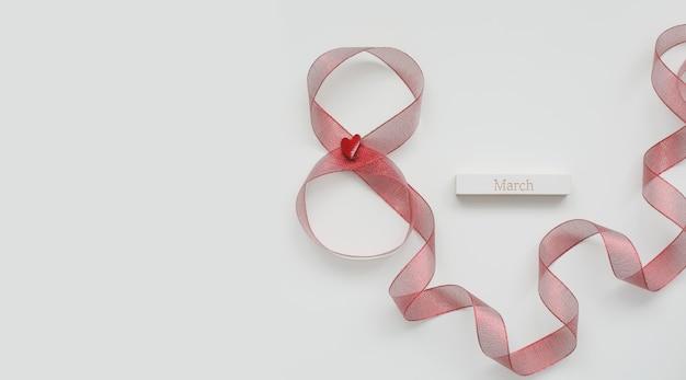 Ruban rouge et mot mars sur fond blanc. 8 mars, concept de la journée internationale de la femme.