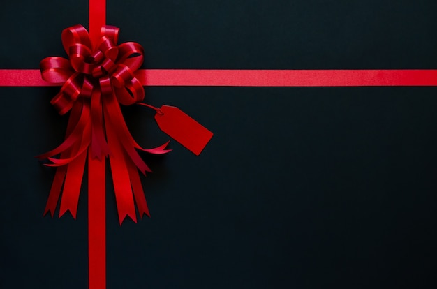 Ruban rouge avec noeud et étiquette de prix sur fond noir