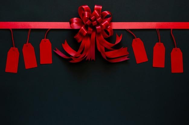 Ruban rouge avec noeud et étiquettes de prix sur fond noir.