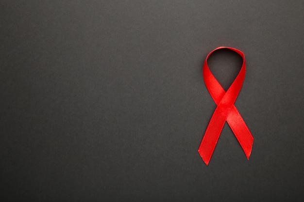 Ruban rouge de sensibilisation au sida sur une surface noire