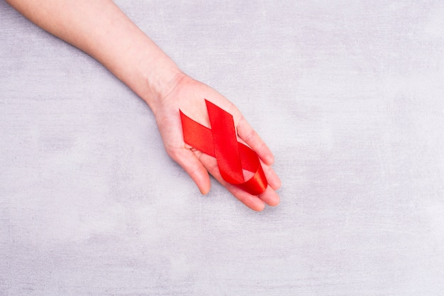 Ruban rouge sur le soutien de la main de la femme pour la journée mondiale du sida