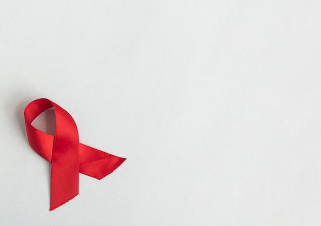 Ruban rouge tourbillonnant pour le sida et la journée du vih sur un noeud en satin sur fond bleu avec place pour le texte