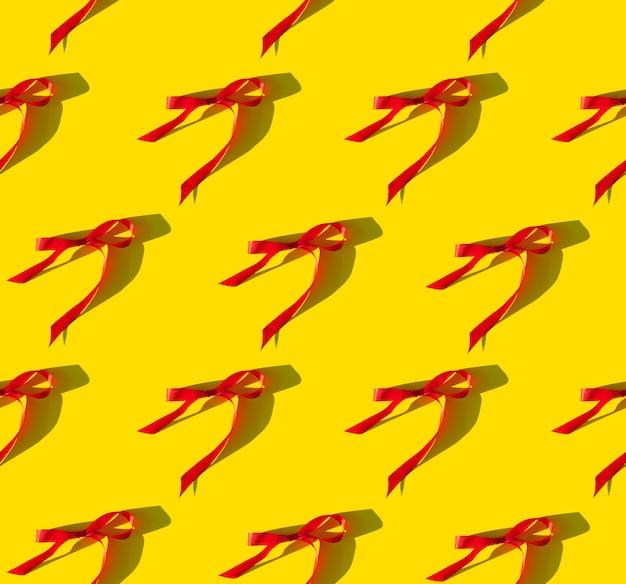 Ruban rouge vif sur fond jaune cadeau de célébration du nouvel an et motif de vacances
