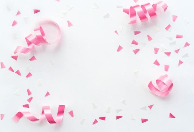 Ruban roulant rose et confettis sur fond blanc avec espace de copie pour la conception du carnaval du festival