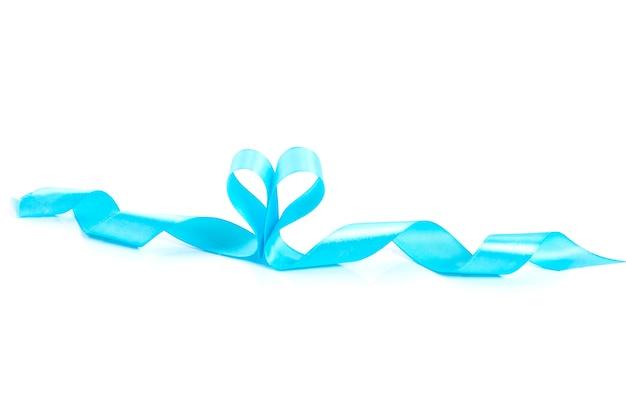 Ruban de satin bleu vif sur surface blanche