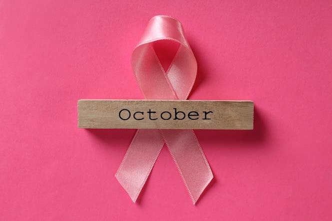 Ruban de sensibilisation au cancer du sein et bloc de bois avec texte octobre sur fond rose