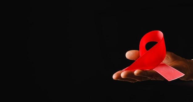 Ruban de sensibilisation à la journée mondiale du sida, vieilles mains féminines tenant un ruban rouge