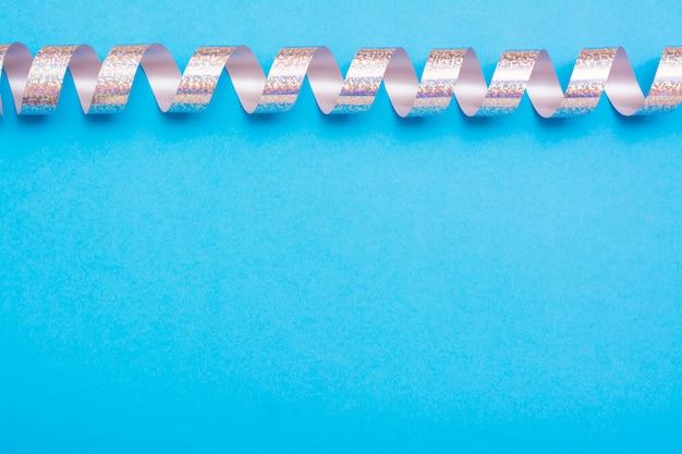 Ruban serpentine argent brillant sur un fond bleu. vue de dessus