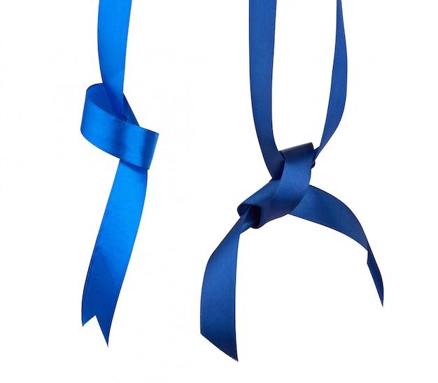 Ruban de soie bleu et bleu foncé suspendu à un nœud et isolé sur blanc
