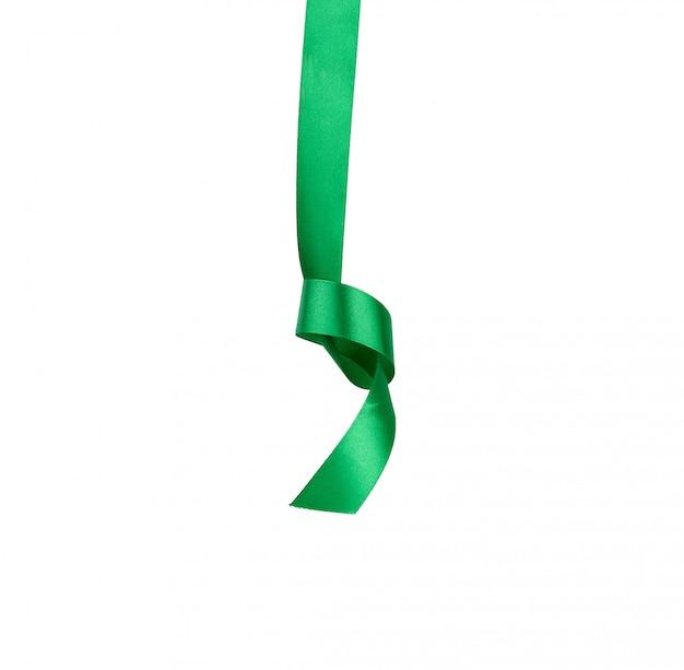 Ruban de soie vert suspendu à un nœud et isolé sur blanc