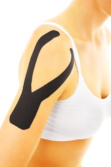 Ruban spécial physio mis sur les muscles d'un bras blessé sur fond blanc