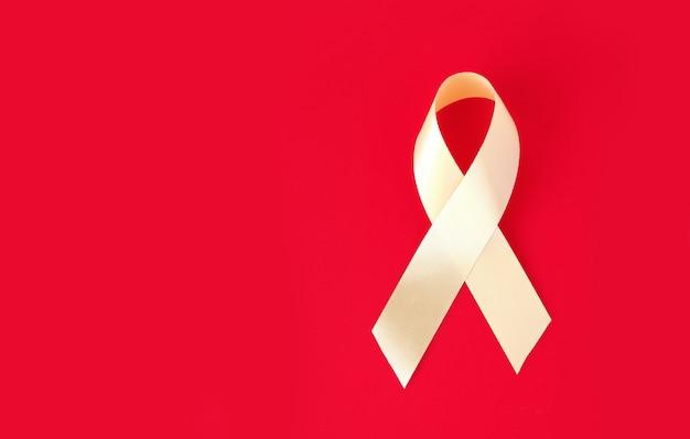 Ruban symbolique or sur une surface rouge