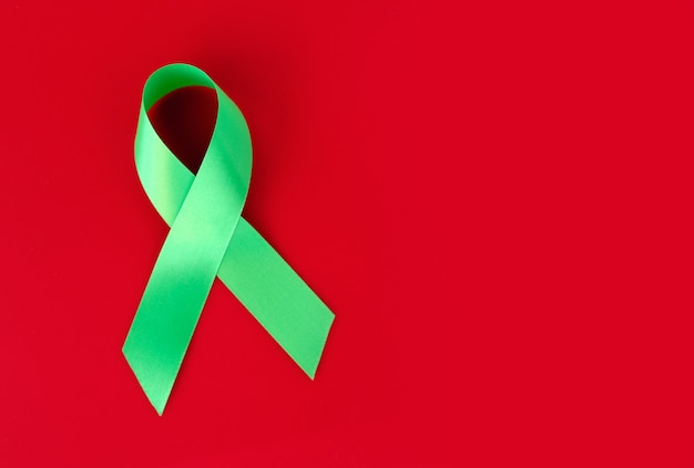 Ruban symbolique vert sur une surface rouge