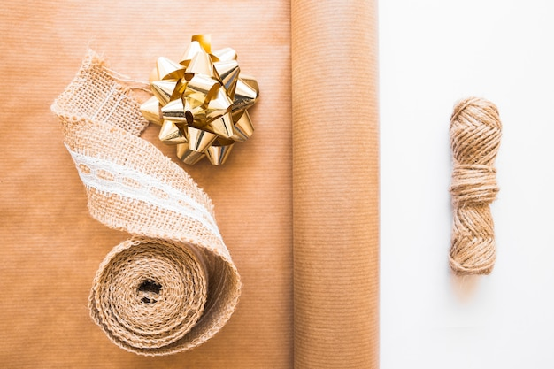 Ruban de tissage; arc d'or; papier cadeau marron et chaîne de jute sur fond blanc