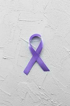 Ruban violet sur fond de plâtre