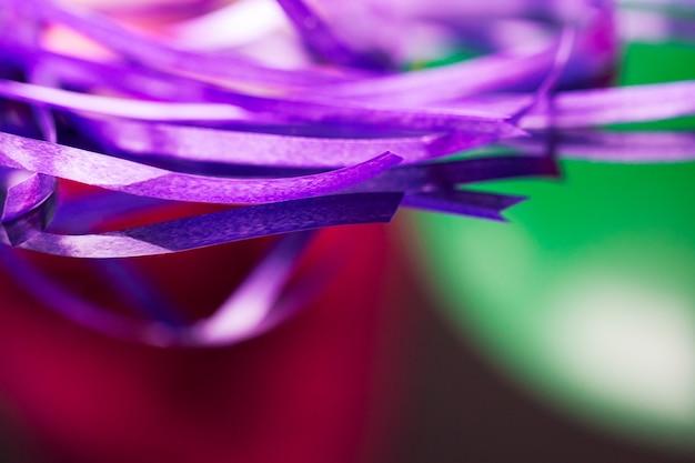 Ruban washi violet pour travaux manuels sur un arrière-plan flou rouge et vert.
