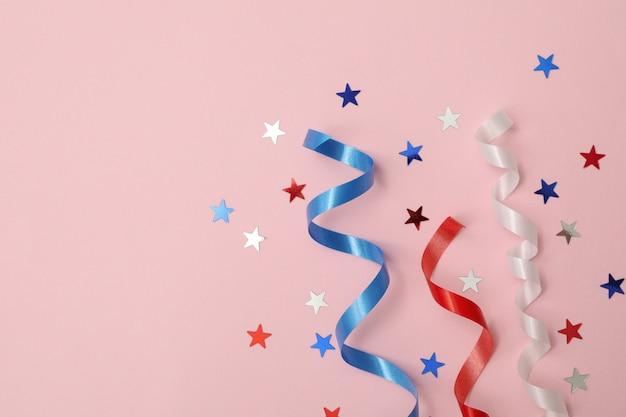 Rubans bouclés blancs, rouges et bleus et étoiles sur surface rose