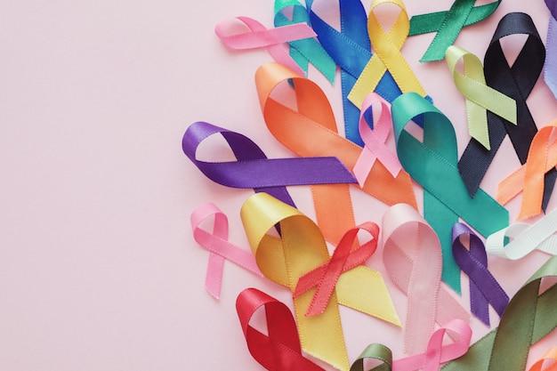 Rubans colorés sur fond rose, sensibilisation au cancer, journée mondiale contre le cancer