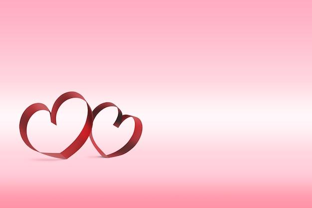 Rubans en forme de coeurs sur fond rose
