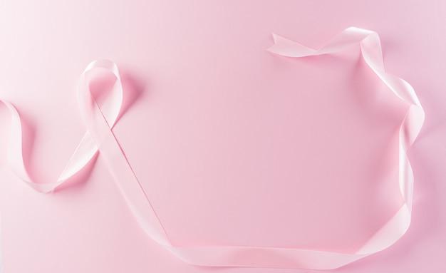 Rubans roses sur fond pastel symbole de la sensibilisation au cancer du sein chez les femmes