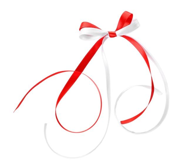 Rubans rouges et blancs colorés avec un arc isolé sur blanc