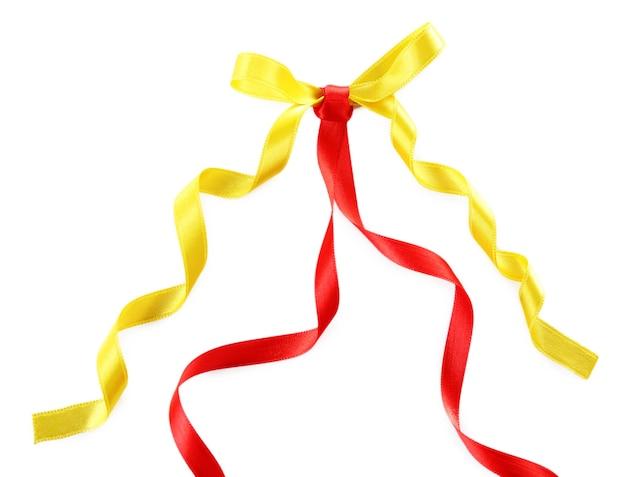 Rubans rouges et jaunes colorés avec un arc isolé sur blanc