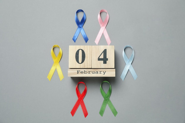 Rubans de sensibilisation multicolores et calendrier avec 4 février sur gris