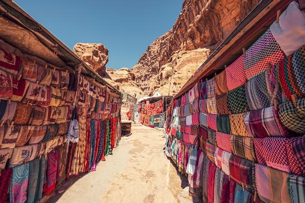 Rue commerçante avec marché dans l'ancienne ville de petra en jordanie avec des produits souvenirs, des tissus et des tapis avec des ornements bédouins nationaux