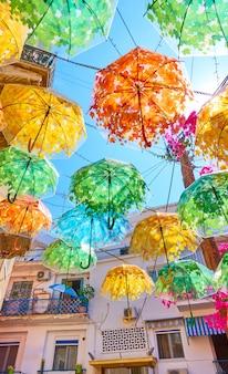 Rue décorée de parapluies colorés dans la ville d'égine le jour ensoleillé d'été, île d'égine, grèce