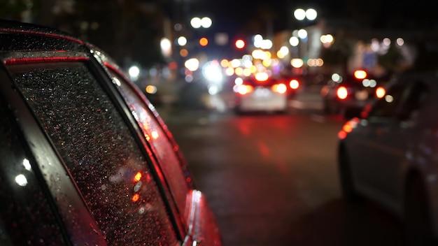 Rue du soir défocalisé, bokeh flou. lumières de la ville et des voitures la nuit pluvieuse. reflet des lampes électriques. automobiles sur route en flou artistique. ville illuminée par le crépuscule, oceanside, california usa.