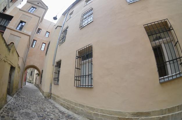 Rue étroite avec un chemin de pavés. passage entre les anciens gratte-ciel historiques de lviv, en ukraine