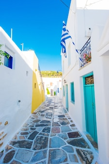 Rue étroite avec trottoir dallé et maisons rustiques traditionnelles sur l'île de paros, grèce