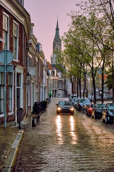 Rue pavée de delft avec voiture sous la pluie