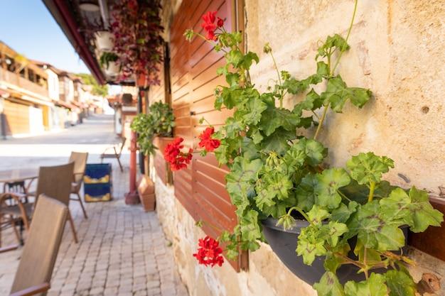 Rue pavée de la vieille ville avec des tables vides dans le café de la rue, des fleurs tôt le matin, side, turquie. photo de haute qualité