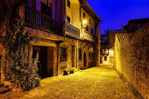 Rue pittoresque de maisons en pierre avec balcons et lampadaires la nuit.