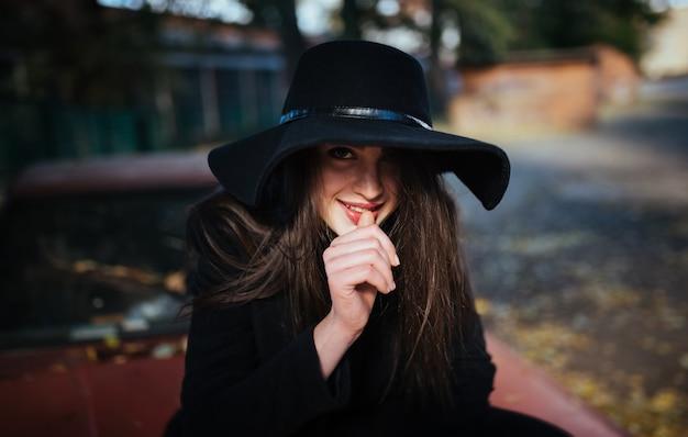 Rue portrait de jeune femme décontractée en chapeau avec, vêtements noirs, lèvres rouges