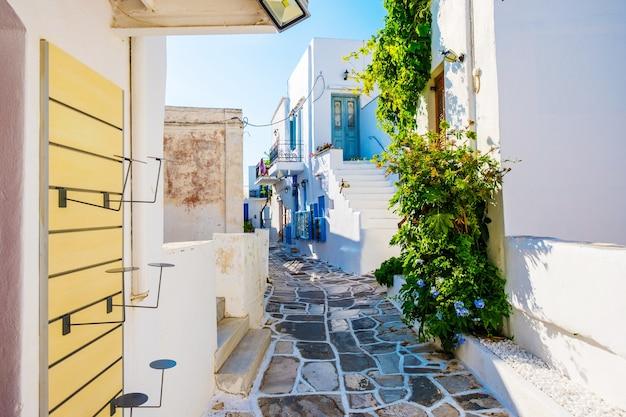 Rue traditionnelle tranquille du village de lefkes avec des maisons blanches et des plantes vertes, paros, grèce