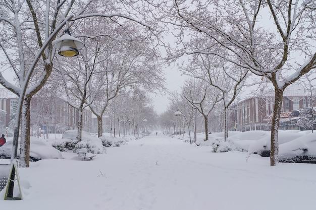 Rues et bâtiments couverts de neige par jour en raison de la tempête de neige filomena tombant à madrid en espagne. les gens qui marchent dans la neige. espagne
