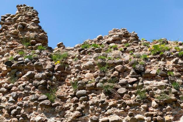 Ruiné et envahi par les ruines d'herbe d'une ancienne forteresse et de pierres et de briques, ruines de structures défensives du moyen âge