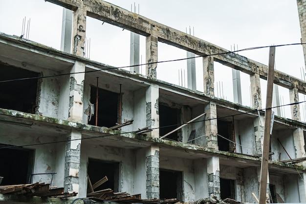Les ruines d'un ancien bâtiment en panneaux faits de blocs de béton avec des fenêtres vides.