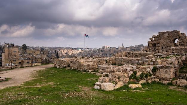 Les ruines de la citadelle sur la ville d'amman en jordanie avec drapeau du pays